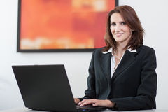 Businesswoman uses laptop Royalty Free Stock Image