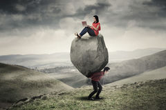 Businesswoman uses laptop on the stone. Asian businesswoman sitting on the stone and using laptop computer while his partner carrying the stone on the hill Stock Photo