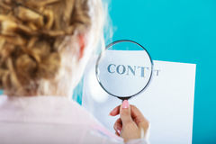 Businesswoman uses magnifying glass to check contract. Closeup businesswoman uses magnifying glass to check contract, rear view on blue background Royalty Free Stock Photo