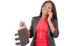 Businesswoman uses mobile phone after shopping. Happy businesswoman holding shopping bags talking on the phone on white background Royalty Free Stock Image