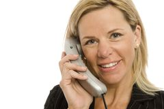 Businesswoman uses phone. Businesswoman in a suit uses a corded telephone Stock Image