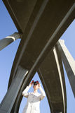 Businesswoman using binoculars beneath overpasses, low angle view Royalty Free Stock Image