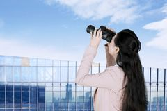 Businesswoman using binoculars at outdoors royalty free stock images