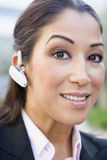 Businesswoman using bluetooth earpiece. Outside Royalty Free Stock Images
