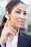 Businesswoman using bluetooth earpiece stock photo