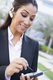 Businesswoman using bluetooth earpiece and PDA. Outside Stock Photos