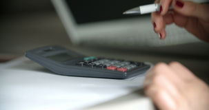 Businesswoman using calculator in office. Close up of a young businesswoman using calculator in office. Corporate, financial background stock footage