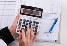 Businesswoman Using Calculator At Office Desk Stock Photography