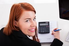 Businesswoman Using Calculator At Office Desk Stock Images