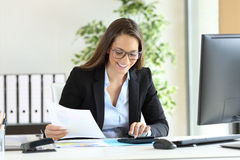 Businesswoman using a calculator at office. Happy businesswoman wearing suit working using a calculator in a desk at office Stock Photos
