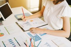 Businesswoman using a calculator to calculate the numbers discus. Sing the charts and graphs showing the results of their successful. Accounting,Finances and royalty free stock photography
