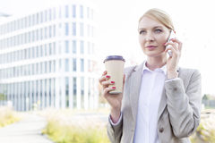 Businesswoman using cell phone while holding disposable cup outdoors Royalty Free Stock Photography