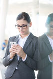 Businesswoman using cell phone while leaning on glass wall Royalty Free Stock Photography