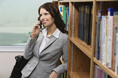 Businesswoman Using Cell Phone In Library Royalty Free Stock Photo