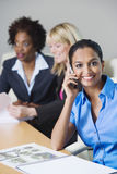 Businesswoman Using Cell Phone During meeting Stock Photography