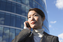 Businesswoman Using Cellphone Against Office Building Royalty Free Stock Image