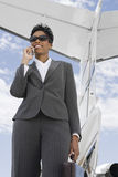 Businesswoman Using Cellphone At Airfield Stock Images