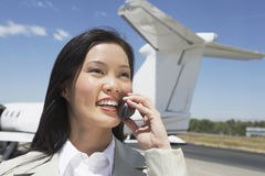 Businesswoman Using Cellphone With Airplane In Background Royalty Free Stock Images