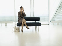Businesswoman Using Cellphone At Airport Lobby Stock Photos