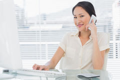 Businesswoman using cellphone and computer at desk Stock Images
