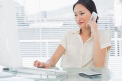 Businesswoman using cellphone and computer at desk Royalty Free Stock Image