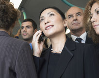 Businesswoman Using Cellphone In Crowd On Train. Closeup of a businesswoman using mobile phone in train amid commuters Stock Image