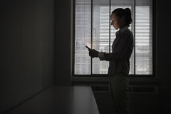 Businesswoman Using Cellphone In Dark Office Stock Photos