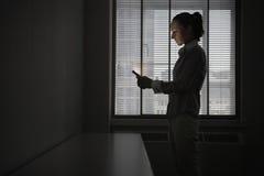Businesswoman Using Cellphone In Dark Office Stock Photos