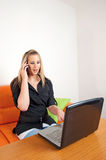 Businesswoman using a cellphone and laptop Royalty Free Stock Photos