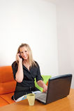 Businesswoman using a cellphone and laptop Stock Photo