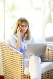 Businesswoman using cellphone and laptop Royalty Free Stock Photo
