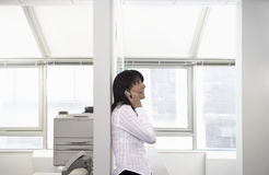 Businesswoman Using Cellphone Leaning On Partition Stock Photography