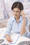 Businesswoman using cellphone in office Royalty Free Stock Photo