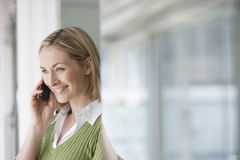 Businesswoman Using Cellphone In Office Stock Photo