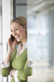 Businesswoman Using Cellphone In Office Stock Images