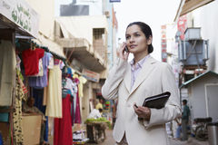 Businesswoman Using Cellphone On Street. Young businesswoman using cell phone on city street Royalty Free Stock Photo