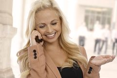 Businesswoman talking on cellphone on street Royalty Free Stock Images
