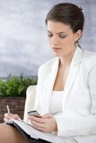 Businesswoman using cellphone, writing notes stock photo