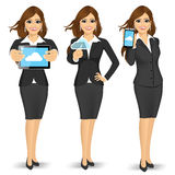 Businesswoman using cloud computing on different devices Royalty Free Stock Images
