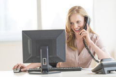 Businesswoman Using Computer While Conversing On Landline Phone Stock Photo