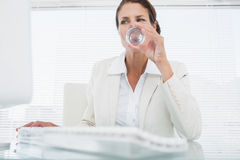 Businesswoman using computer while drinking water Royalty Free Stock Image