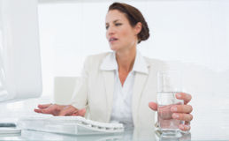 Businesswoman using computer while holding a glass of water Royalty Free Stock Photos