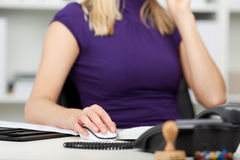 Businesswoman Using Computer Mouse At Desk Stock Image