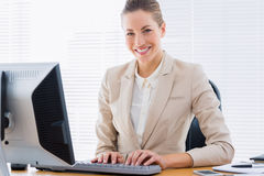 Businesswoman using computer at office desk Stock Photos