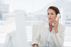 Businesswoman using computer and phone Stock Photo