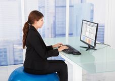 Businesswoman using computer while sitting on fitness ball Stock Photos
