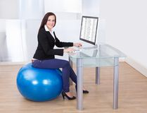 Businesswoman using computer while sitting on pilates ball Stock Photography