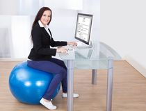 Businesswoman using computer while sitting on pilates ball Stock Image
