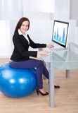Businesswoman using computer while sitting on pilates ball Royalty Free Stock Image