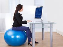 Businesswoman Using Computer While Sitting On Pilates Ball Stock Images